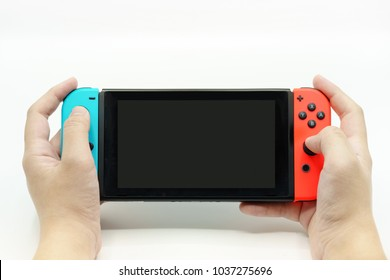 Bangkok Thailand - March 1, 2018: A man holding a Nintendo Switch video game system with white background, the new console game in japan released by Nintendo Co., Ltd. in 2017.