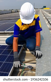 Bangkok, Thailand - March 14,2021 : A technician installing solar panel on the factory roof, on March 14,2021 in Bangkok, Thailand