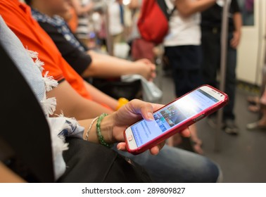 BANGKOK, THAILAND- MARCH 16: Unknown people uses mobile phone while travel by subway on March 16, 2015 in Bangkok, Thailand. It's a people's behavior to entertain when they take public transportation.