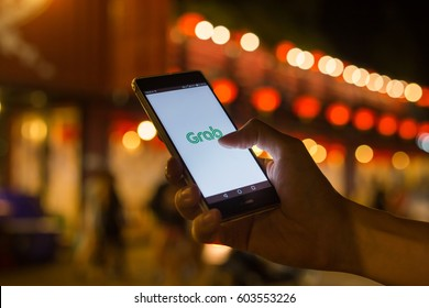BANGKOK, THAILAND - MARCH 17, 2017. GRAB application display on mobile screen in male hand's while he calling some GRAB at night street (soft focus and a little noise from night shoot)