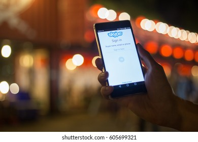 BANGKOK, THAILAND - MARCH 17, 2017. SKYPE application display on mobile screen in male hands, A man trying to lock in Skype  (soft focus and little noise from night shoot)