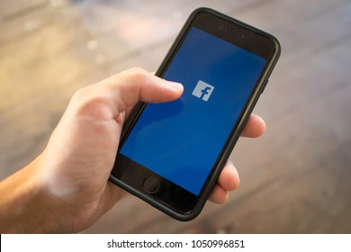 Bangkok, Thailand - March 17, 2018 : iPhone 7 held in one hand showing its screen with Facebook logo.