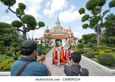 BANGKOK, THAILAND - March 17, 2018 : Tourists take pictures an ancient Giant statues in Wat Arun, Temple of Dawn Thailand.