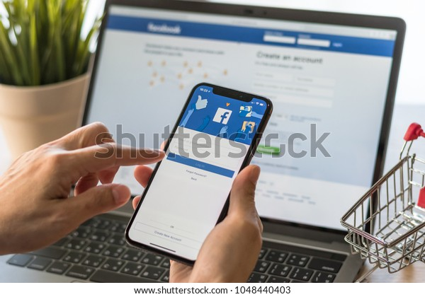 BANGKOK, THAILAND - March 18, 2018: Facebook social media app logo on log-in, sign-up registration page on mobile app screen on iPhone X (10) in person's hand working on e-commerce shopping business
