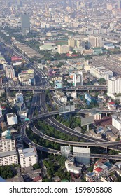 BANGKOK, THAILAND - MARCH 19, 2013: Some of Bangkok's famous expressways seen from above. In the Background are the towers and skyscrapers of the city.