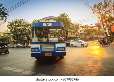 Bangkok, Thailand - March 2, 2017:  Local bus and cars in traffic passes through a busy junction during sunset in Bangkok, Thailand.