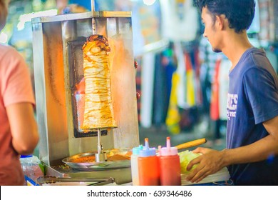 Bangkok, Thailand - March 2, 2017:  Street vendor is selling grilled kebab, the popular street foods at Khao San Road night market, Bangkok, Thailand.
