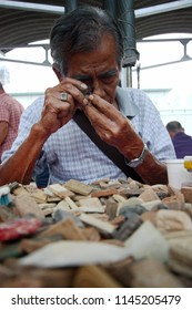 BANGKOK, THAILAND - MARCH 20, 2015 : The old man consider on thai amulets by folding hand loupe.