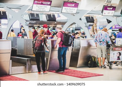 Bangkok, Thailand - March, 2019: Travellers queue up at Qatar Airways check in counter at Suvarnabhumi Airport (VTBS) to have their luggage checked in