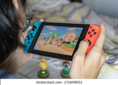 Bangkok, Thailand - March 21, 2020 : A man playing Animal Crossing on Nintendo Switch.