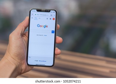 Bangkok, Thailand - March 22 2018: Close up a man hand hold iphone X for searching on google with blurred background. To use searching information from internet.