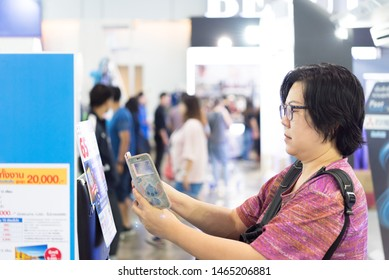 Bangkok, Thailand - March 23, 2019 : Unidentified asian woman feeling happy when her purchase a product and QR code scan by mobile phone in department store or exhibit hall expo