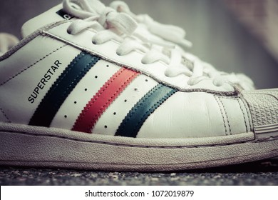 """BANGKOK, THAILAND - MARCH 24, 2018 : Adidas original classic Red, White and Blue """"Tri-Color"""" Superstar old shoes on street, process color."""