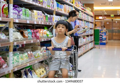 BANGKOK THAILAND - MARCH 24: Unidentified boy stares in boredom on a shopping cart as the mother shops in Foodland supermart in Bangkok on March 24, 2019.