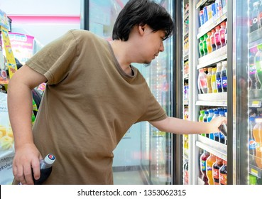 BANGKOK, THAILAND - MARCH 24: Unidentified man selects and purchases Pepsi Cola soft drink in 7-Eleven convenient store on Petchkasem 69 in Bangkok on March 24, 2019.