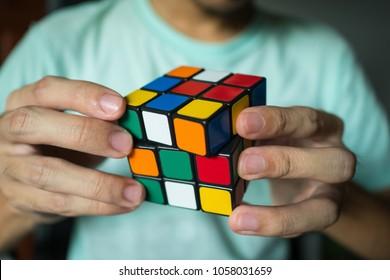 Bangkok, Thailand - March 27, 2018 : A man solving Rubik's cube.