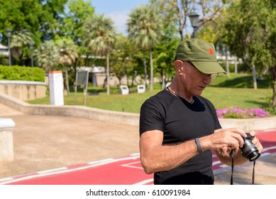 BANGKOK, THAILAND MARCH 28, 2017: Senior tourist traveling and taking photos at Benjakitti park with Canon compact camera in central of Bangkok next to the Queen Sirikit National Convention Center