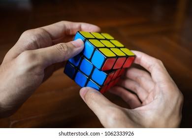 Bangkok, Thailand - March 28, 2018 : A man solving Rubik's cube.