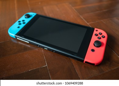 Bangkok, Thailand - March 28, 2018 : Nintendo Switch game console on wooden floor.