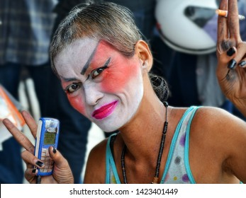 BANGKOK, THAILAND - MARCH 29, 2013: Face-painted Thai genderqueer holds a cell phone in his right hand, a cigarette in his left hand and flashes the double V sign, on March 29, 2013.