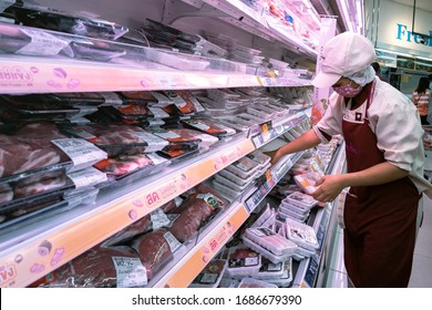Bangkok, Thailand - March 29, 2020 : asian woman shop assistant wearing hygiene face mask are restocking fresh pork and chicken meat to shelf in supermarket at coronavirus pandemic or covid-1 outbreak