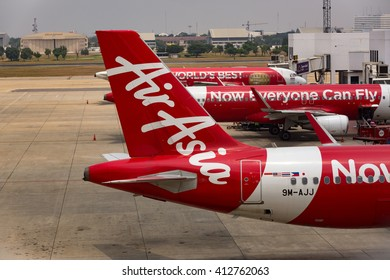 BANGKOK, THAILAND - MARCH 3, 2014: unloading of baggage from the Air Asia aircraft in Bangkok airport. Air Asia company is the largest low cost airlines in Asia.
