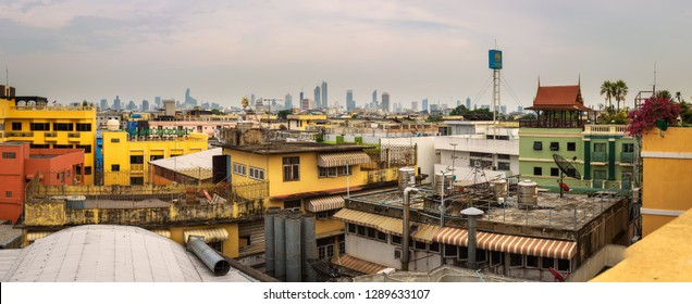 Bangkok, Thailand - March 31, 2018 : Panorama of many roofs of old Bangkok with the modern Bangkok skyline in the background.