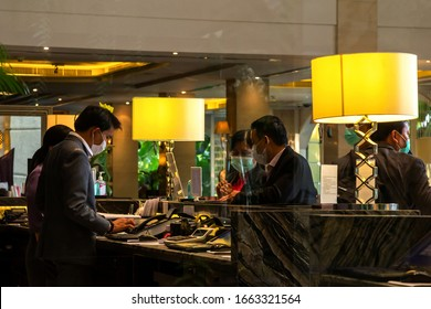 Bangkok, Thailand - March 4, 2020 : asian receptions and business travelers check-in in hotel lobby front desk are wearing hygiene mask to protect from outbreaking of coronavirus or covic 19.