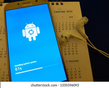 Bangkok, Thailand. March 8, 2019 - android smartphone installing system update in progress. android robot close up on smartphone screen with 2019 year calendar.