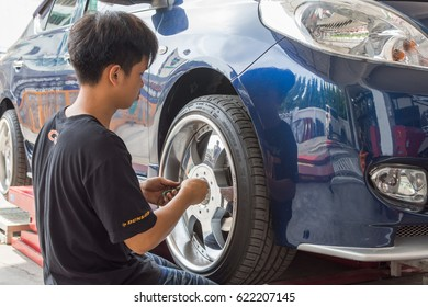 Bangkok, Thailand - March 9, 2017 : Unidentified car mechanic or serviceman disassembly and checking a car alloy chrome wheel for fix and repair suspension problem at car garage or repair shop