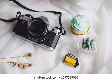 BANGKOK, THAILAND - MAY 05, 2018: Canon AE-1 Program 35mm film camera and a roll of Kodak ProImage 100 film and decorate cupcake, dry flowers and cactus on white Tablecloth. Copy Space