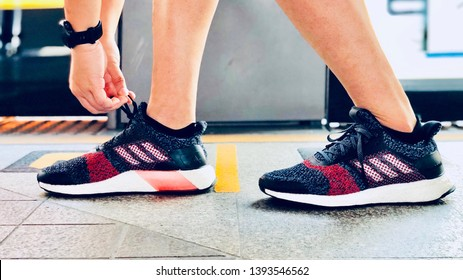 BANGKOK, THAILAND, MAY 07, 2019: The energetic man tighten the laces of running shoes Adidas Ultraboost ST during waiting the BTS train.