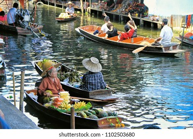 Bangkok, Thailand - May 08, 2018: unidentified tourists and traditional vendors on the famous floating market  in Bangkok. It is a traditional market on the chanels, where they sell goods and food fro