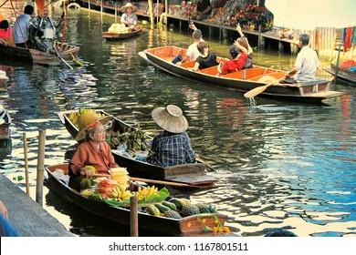 Bangkok, Thailand - May 08, 2018: unidentified tourists and traditional vendors on the famous floating market Damnoen Saduak in Bangkok.