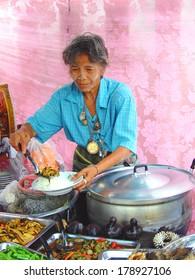 BANGKOK, THAILAND - MAY 1, 2008: Old Thai woman displays hot rice at the market
