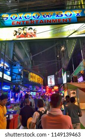 Bangkok, Thailand - May 1, 2017: Adult tourists walking under the information sign at the entrance of Soi Cowboy, one of the red light district areas of Bangkok.