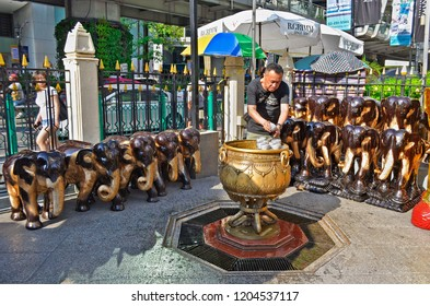 Bangkok, Thailand - May 1, 2017: Thai Buddhist doing ablutions in front of elephant statues at Erawan Shrine.