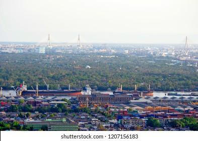 Bangkok,  Thailand - May 1, 2017: High angle view of Bangkok Port, popularly known as Khlong Toei Port, with Bang Kachao and Bhumibol II Bridge in the background.