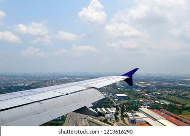 Bangkok, Thailand - May 1, 2017: The Bangkok skyline far away in the background seen from a Thai Smile A320 plane about to land at Suvarnabhumi International Airport.