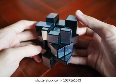 Bangkok, Thailand - May 1, 2018 : Man solving weird shaped Rubik's cube.