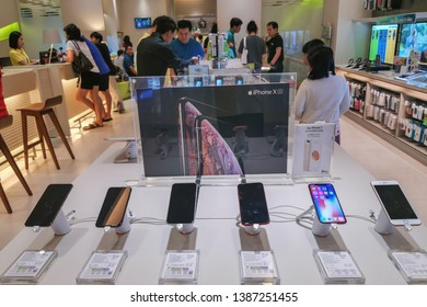Bangkok, Thailand - May 1, 2019 : New mobile smartphone in telecommunication electronic store display showcase and Customers browse smartphones at AIS service mobile.