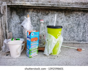 BANGKOK / THAILAND - MAY 1, 2019 : The pile of garbage, cup, milk box, bottle  on the walkway roadside, The people throwing trash carelessly into anywhere not a bin. Environment negligently concept.