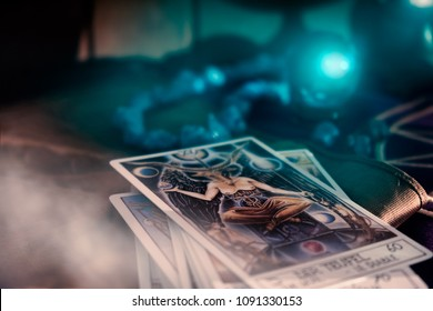 BANGKOK, THAILAND - MAY 11, 2018: View of tarot card and crystal ball on the table. The Devil. Soft focus. Dark tone.