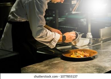 BANGKOK, THAILAND. MAY 12, 2016: Chef plating dish neatly on kitchen counter before serve to customer at hotel in Bangkok, Thailand.