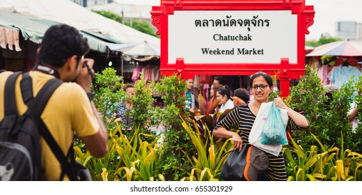 """BANGKOK, THAILAND - MAY 14, 2017: Traveler (supposedly Indian) shows her purchases posing to a friend with a photo camera next to signboard """"Chatuchak Weekend Market"""" (in English and Thai scripts)"""
