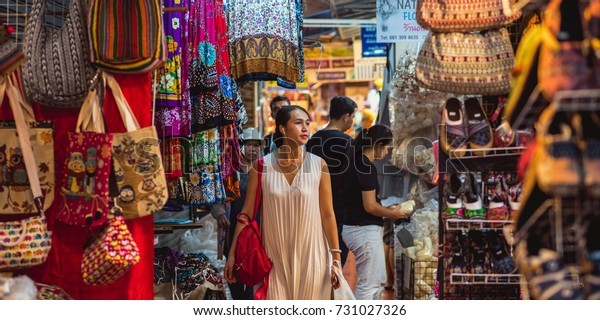 Bangkok, Thailand - May 14, 2017: Young Asian woman (unidentified) walks with headphones along stalls and stands of Chatuchak market. The market is a very popular shopping area in Bangkok.
