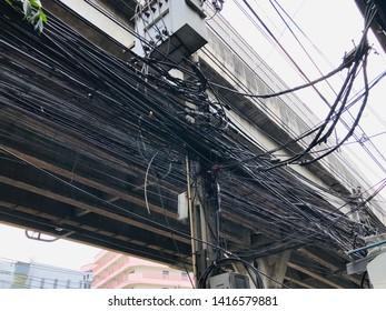 Bangkok, Thailand - May 14, 2019 : Close up confusion electric wire at Bangkok Thailand.Messy electrical cables under motorway.