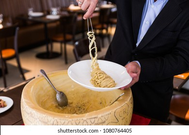 BANGKOK, THAILAND. MAY 17, 2016: Chef neatly plating spaghetti carbonara in cheese wheel on white plate at the restaurant in Bangkok, Thailand.