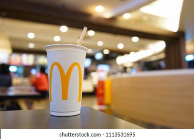 Bangkok, Thailand - May 17, 2018 : Cup of McDonald's Cola with Straw in the background of the McDonald's restaurant. McDonald's Corporation is the world's largest fast food restaurants.