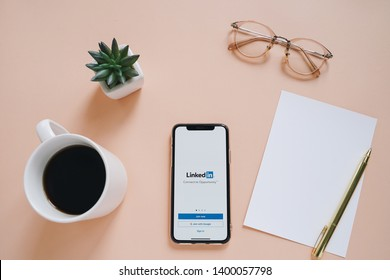 BANGKOK, THAILAND - May 17,2019: Flat lay of workspace desk and Apple iPhone XS with LinkedIn application on the screen. LinkedIn is a business-oriented social networking service.